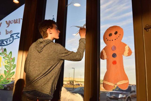 Elida High School students show their artistic capabilities while painting  the windows of Mellow Mushroom. Submitted