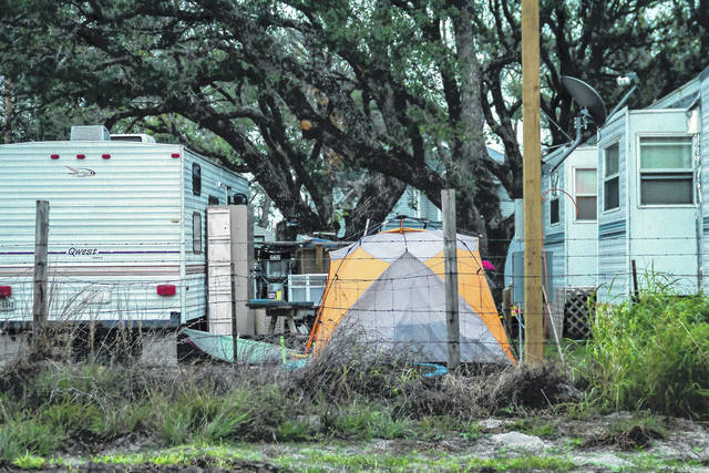In this Dec. 15, 2017 photo provided by Kim Porter, shows people living in tents and trailers in Rockport, Texas. The federal government typically spends up to $150,000 apiece — not counting utilities, maintenance or labor — on the trailers it leases to disaster victims, then auctions them at cut-rate prices after 18 months of use or the first sign of minor damage. Officials have continued the practice even amid a temporary housing shortage in Texas, where almost 8,000 applicants are still awaiting federal support nearly four months after Hurricane Harvey landed in the Gulf Coast.