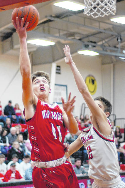 Wapakoneta's Aaron Good put up a shot against Bluffton's Jared Piercefield during Friday night's game in Bluffton. See more game photos at LimaScores.com.