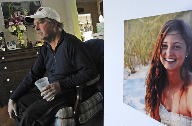 FILE - In this Jan. 23, 2014 file photo, James Holleran, father of Madison Holleran, a University of Pennsylvania freshman who took her own life, talks about his daughter while sitting next to a favorite photo of her at his home in Allendale, N.J. Nearly half of the largest U.S. public universities do not track suicides among their students, despite making investments in prevention at a time of surging demand for mental health services. After her 2014 suicide, one of her former teachers in New Jersey was surprised to learn learn many universities don't report suicide statistics. (April Saul/The Philadelphia Inquirer via AP, File)