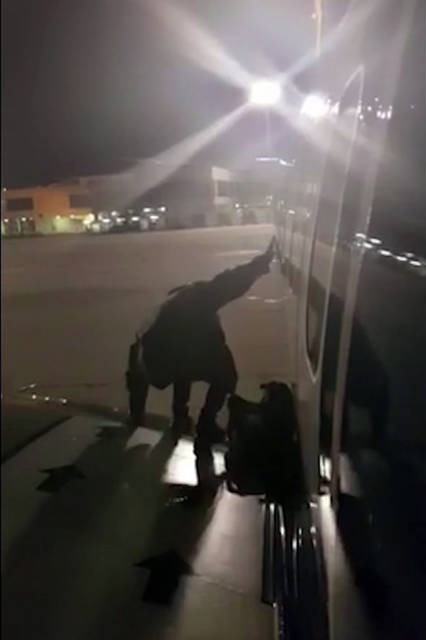 A Ryanair passenger who apparently got fed up waiting to get off the plane stands on the wing of a Ryanair plane at Malaga airport, Spain, Monday Jan. 1, 2018, filmed by another passenger.  After various delays in the flight from London's Stansted Airport, the passenger, who has not been named, used the emergency exit to climb onto the wing. (Fernando del Valle Villalobos via AP)