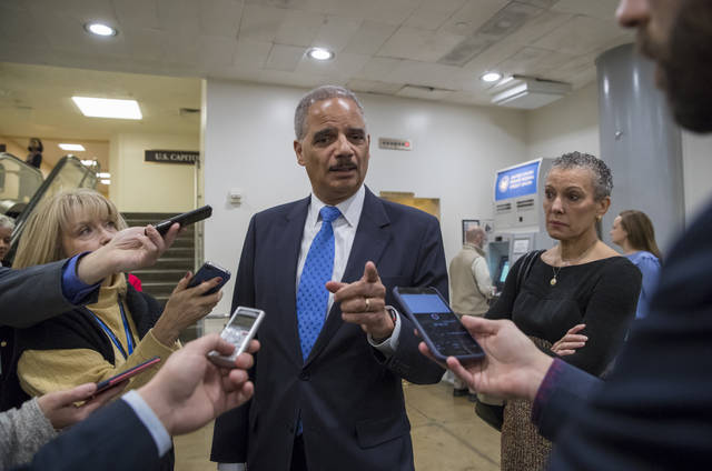 """Former Attorney General Eric Holder takes questions from reporters at the Capitol where he attended the swearing-in of Sen. Doug Jones, D-Ala., in Washington, Wednesday, Jan. 3, 2018. Holder says he is """"deeply disturbed"""" that Attorney General Jeff Sessions hasn't spoken out to defend his employees at the Justice Department amid Republican criticism of the FBI. At far right is Holder's wife, Sharon Malone. (AP Photo/J. Scott Applewhite)"""