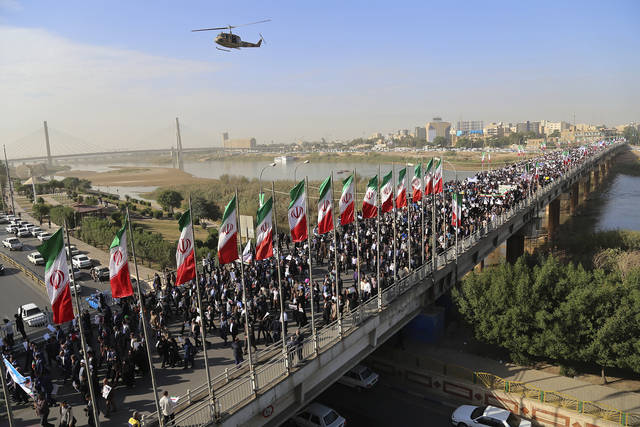 In this photo provided by Mehr News Agency, demonstrators attend a pro-government rally in the southwestern city of Ahvaz, Iran, Wednesday, Jan. 3, 2018. Tens of thousands of Iranians took part in pro-government demonstrations in several cities across the country on Wednesday, Iranian state media reported, a move apparently seeking to calm nerves after a week of protests and unrest that have killed at least 21 people. (Mehdi Pedramkhoo/Mehr News Agency via AP)