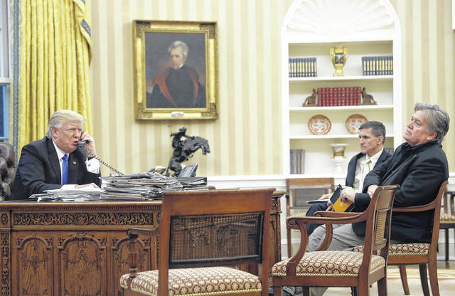 """In this Jan. 28, 2017, file photo, President Donald Trump speaks on the phone with Prime Minister of Australia Malcolm Turnbull, with then-National Security Adviser Michael Flynn, center, and then- chief strategist Steve Bannon, right, in the Oval Office of the White House in Washington. Trump responded to criticism leveled at him in a new book that says he never expected — or wanted — to win the White House, his victory left his wife in tears and a senior adviser thought his son's contact with a Russian lawyer during the campaign was """"treasonous."""""""