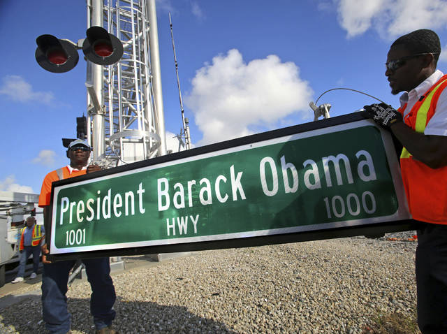 "FILE - In this Thursday, Dec. 17, 2015 file photo, Dale Moncur, left, and Cedric Anderson of Palm Beach County Traffic Operations, hold a sign for the new President Barack Obama Highway in preparation to change it from the ""Old Dixie Highway"" in Riviera Beach, Fla. On Friday, Jan. 5, 2018, The Associated Press reported that stories circulating on the internet about President Donald Trump ordering the name of the highway changed back to ""Old Dixie"" are untrue. (Lannis Waters/Palm Beach Post via AP)"