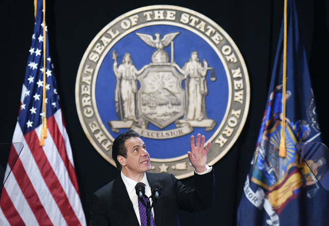 """FILE - In this Wednesday, Jan. 3, 2018 file photo, New York Gov. Andrew Cuomo makes reference to his father Mario Cuomo as he delivers his state of the state address at the Empire State Plaza Convention Center in Albany, N.Y. During the speech, Cuomo pledged to sue over the new federal tax plan, which he called """"an assault"""" by the federal government. (AP Photo/Hans Pennink)"""