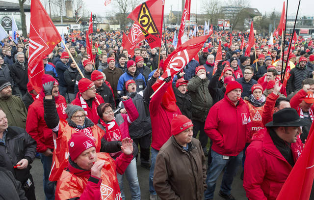 Metalworkers demonstrate in Schweinfurt, southern Germany, Tuesday, Jan. 9, 2018. Germany's largest industrial union pressed its demands for pay rises and the possibility for reduced work hours for its 3.9 million members with renewed short-term strikes Tuesday, saying the economy's steady growth justifies better compensation and conditions.  (Timm Schamberger/dpa via AP)