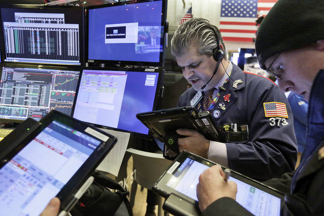 Traders John Panin, center, and Kevin Walsh work on the floor of the New York Stock Exchange, Tuesday, Jan. 9, 2018. Stocks are opening higher on Wall Street, led by gains in health care and financial companies. (AP Photo/Richard Drew)