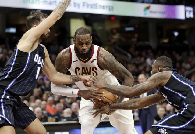 Cleveland Cavaliers' LeBron James, center, drives between Orlando Magic's Evan Fournier, left, and Orlando Magic's Jonathon Simmons during the first half of an NBA basketball game Thursday, Jan. 18, 2018, in Cleveland. (AP Photo/Tony Dejak)