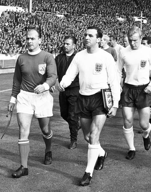 FILE - This is a Oct. 23, 1963 file photo of England captain Jimmy Armfield, front right,  leading out England for the match against the Rest of the World led by Alfredo Di Stefano, front left,  for the Football Association Centenary soccer match at Wembley Stadium, London.  Jimmy Armfield, a former England captain who led Leeds to the European Cup final as a manager before a distinguished career in broadcasting,  died Monday Jan. 22, 2018. He was 82. (AP Photo/File)