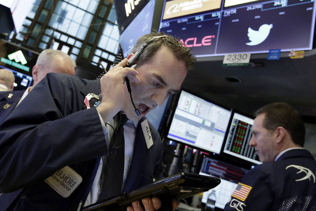 Trader Gregory Rowe, left, and specialist Glenn Carell work on the floor of the New York Stock Exchange, Monday, Jan. 29, 2018. The major U.S. stock indexes are down slightly in early trading Monday, as losses in technology companies outweighed gains elsewhere. (AP Photo/Richard Drew)