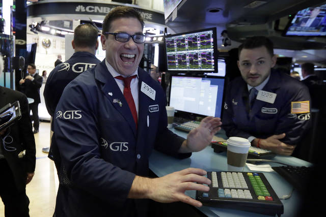 Specialist Robert Tuccillo, left, works at his post on the floor of the New York Stock Exchange, Wednesday, Jan. 31, 2018. Stocks are opening solidly higher on Wall Street after a number of big U.S. companies reported strong quarterly earnings. (AP Photo/Richard Drew)