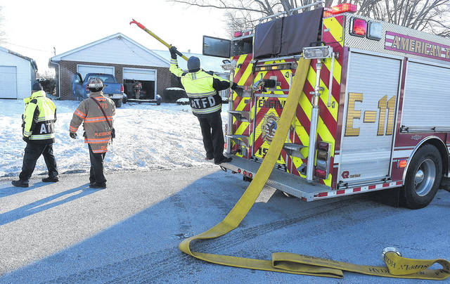 American Township firefighters attend to an attic fire at 1826 North Eastown Road on Tuesday morning. Craig J. Orosz | The Lima News