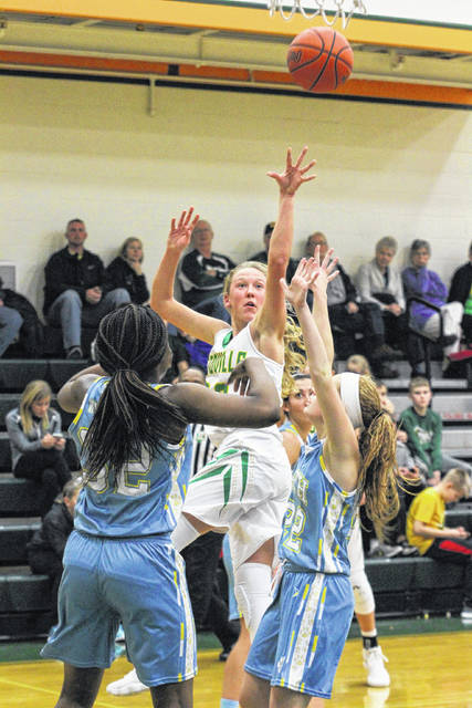 Ottoville's Kasey Knippen puts up a shot against Bath's Elyssabette Andrews, left, and Chandler Clark during Tuesday night's game at Ottoville.