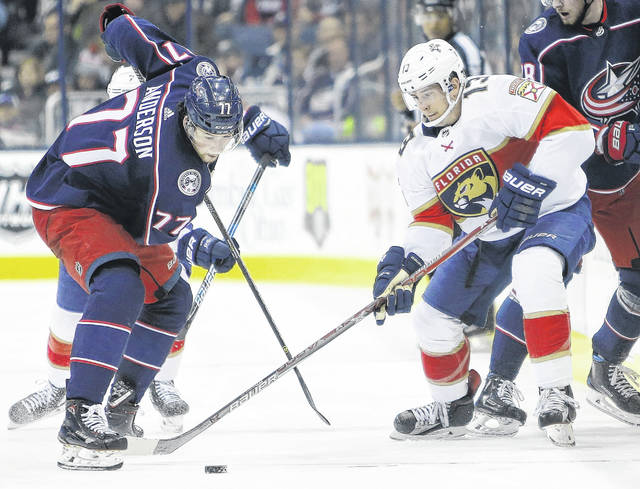 Columbus Blue Jackets' Josh Anderson, left, tries to take the puck away from Florida Panthers' Mark Pysyk during the second period of an NHL hockey game Sunday.