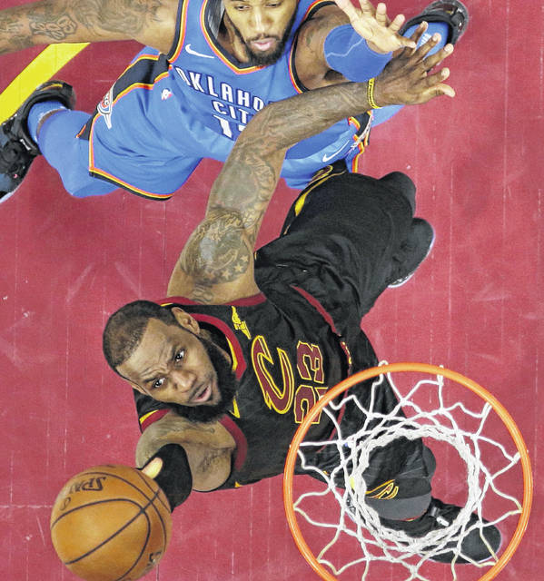 Cleveland Cavaliers' LeBron James, left, drives to the basket against Oklahoma City Thunder's Paul George in the first half of an NBA basketball game, Saturday, Jan. 20, 2018, in Cleveland. (AP Photo/Tony Dejak)