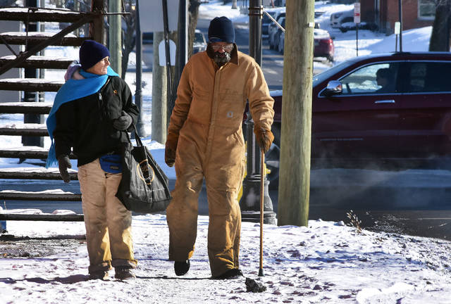 Jeff Maddox, right, of Lima, takes a chilly walk with his friend, Allie, along Kibby Street on Tuesday. Maddox suffered with health issues last year and likes to take a walk for daily exercise.