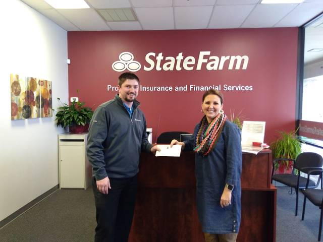 "Steven Slusser, of Van Wert, won Ohio City's Pride 2017 ""Holiday Lights"" contest for Van Wert County and receives his prize money from Tisha Fast of State Farm."