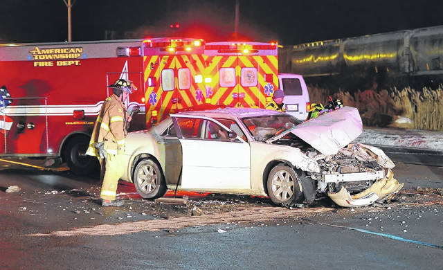 American Township Fire Department officials deal with the aftermath of a car crash on Elida Road Thursday night.