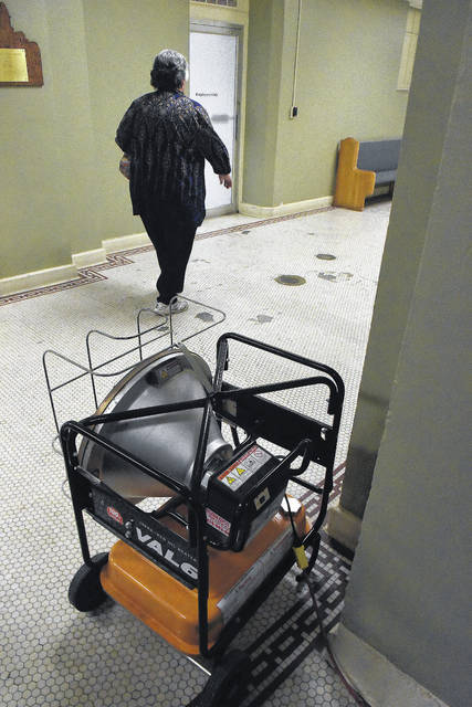 A county employee walks past a portable heater in the hallway of the Allen County Courthouse on Wednesday.