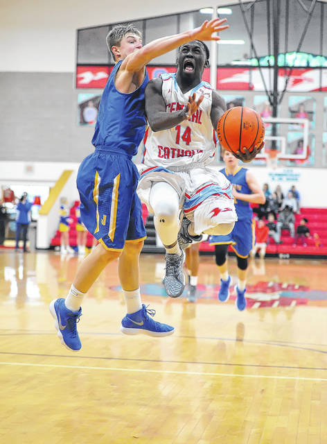 Lima Central Catholic's Jaron Banks is smothered Delphos St. John's Collin Will as he tries to go to the basket during Sunday's game at Msgr. Edward C. Herr Gymnasium. Banks led the Thunderbirds in scoring with 14 points.