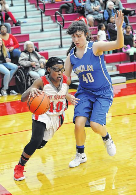 Lima Senior's Nakiya Sigman drives against Findlay's Chloe Holliday during Thursday night's game at Lima Senior High School.