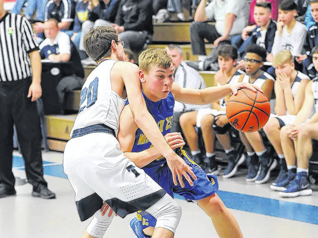 Miller City's Luke Lammers drives against Temple Christian's Dawson Draper during Saturday night's game at Temple Christian.