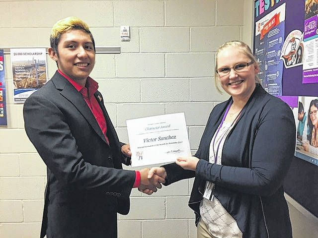 Leipsic High School Guidance Counselor Julie Recker, right, presents a monthly Character Award to senior Victor Sanchez.