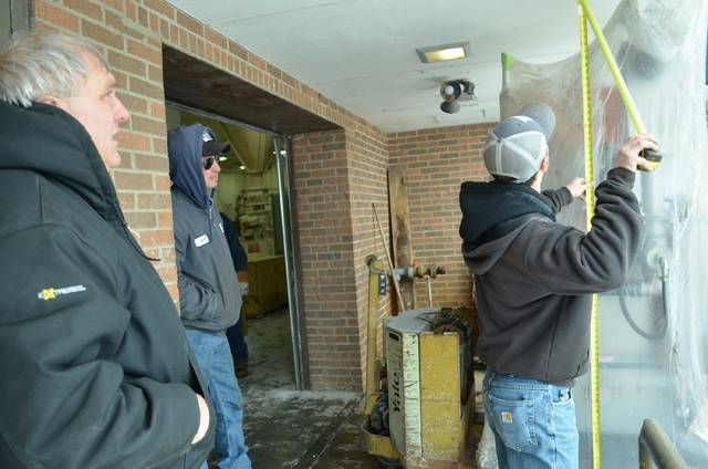 Doug Schroeder (left), Ottawa Water Treatment Plant director, and Jeff Heringhaus, second shift class 3 plant operator, watch as Cody Karpiak, of Chemco Systems, Inc., makes certain there's enough room in the loading dock door for the new lime slaker, delivered Monday, to fit through the door.