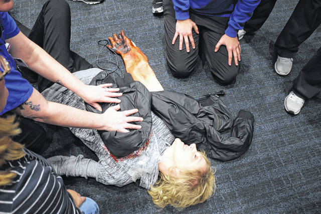 """Health Sciences students at Rhodes State tend to the """"injured"""" during a mock explosion."""