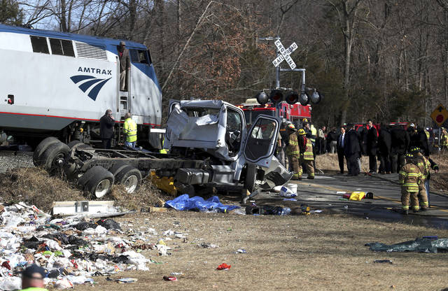 """FILE - In this Wednesday, Jan. 31, 2018 file photo, emergency personnel work at the scene of a collision between an Amtrak passenger train carrying dozens of GOP lawmakers and a garbage truck in Crozet, Va. On Friday, Feb. 2, 2018, The Associated Press has found that stories circulating on the internet claiming the accident was a """"deep state"""" assassination attempt are untrue. (Zack Wajsgrasu/The Daily Progress via AP)"""