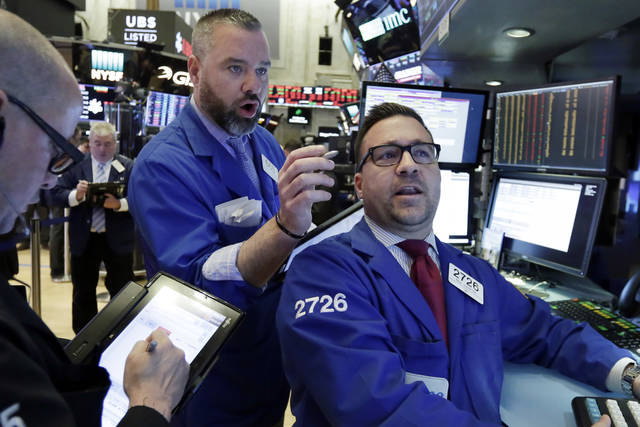 Trader Kevin Lodewick, center, and specialist Paul Cosentino, right, work on the floor of the New York Stock Exchange, Tuesday, Feb. 6, 2018. The Dow Jones industrial average fell as much as 500 points in early trading, bringing the index down 10 percent from the record high it reached on Jan. 26. The DJIA quickly recovered much of that loss. (AP Photo/Richard Drew)