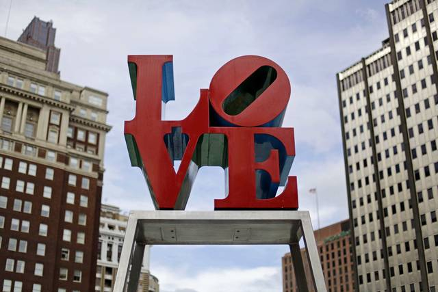 FILE - This Nov. 10, 2010, file photo, shows artist Robert Indiana's LOVE sculpture in John F. Kennedy Plaza, also known as Love Park, in Philadelphia. The sculpture, temporarily relocated in 2016 before renovations to the plaza, is set to return to its traditional location Tuesday, Feb. 13, 2018, ahead of Valentine's Day. The tourist attraction has been repainted to its original colors and will be installed on a new rectangular pedestal, in keeping with how Indiana's other works are displayed. (AP Photo/Matt Rourke, File)