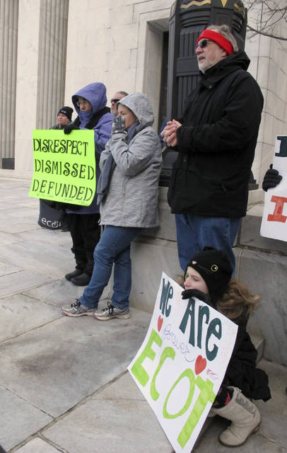 Student Isabella Stephen, of Streetsboro, front right, and teacher Lawana Partlow, of Tallmadge, hold signs among fellow supporters of the Electronic Classroom of Tomorrow during a rally outside the Ohio Supreme Court building, Tuesday, Feb. 13, 2018, in Columbus, Ohio, as the court hears arguments in ECOT's legal dispute with the state. The now-closed e-school has challenged how state officials tallied student enrollment and participation to determine ECOT should repay tens of millions of dollars. (AP Photo/Kantele Franko)