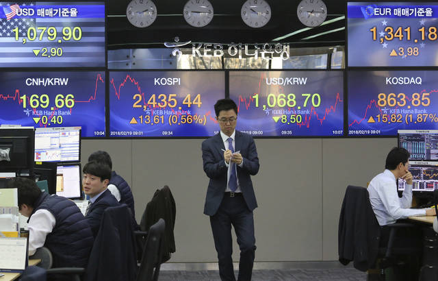 A currency trader passes by screens showing the Korea Composite Stock Price Index (KOSPI) and the exchange rate of South Korean won against the U.S. dollar, center right, at the foreign exchange dealing room of the KEB Hana Bank headquarters in Seoul, South Korea, Monday, Feb. 19, 2018. Asian markets were higher on Monday following Wall Street gains last week, as market jitters showed signs of easing. Many major markets were closed on holidays. (AP Photo/Ahn Young-joon)