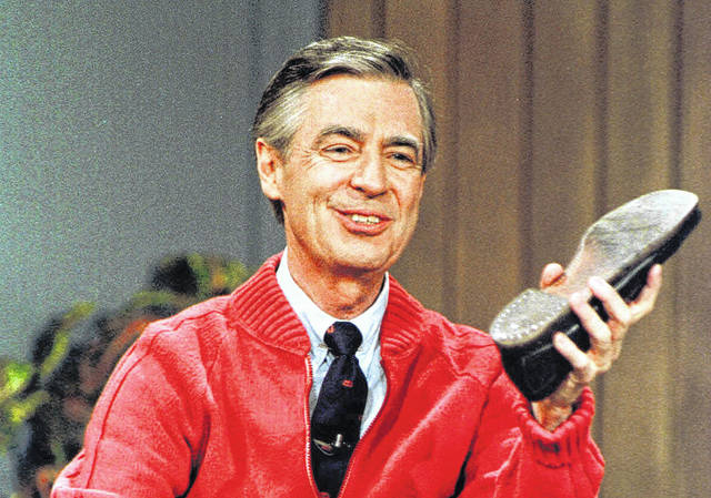"""This June 28, 1989, photo, shows Fred Rogers as he rehearses the opening of his PBS show """"Mister Rogers' Neighborhood"""" during a taping in Pittsburgh. It's been 50 years since Fred Rogers first appeared on our TVs, a gentle and avuncular man who warbled """"Won't You Be My Neighbor?"""""""