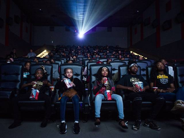"""Mari Copeny, third from left, watches a free screening of the film """"Black Panther"""" with more than 150 children after she raised $16,000 to provide free tickets in an entire theater Monday in Flint Township, Mich. As """"Black Panther"""" debuts in theaters across the U.S., educators, philanthropist, celebrities and business owners are pulling together their resources to bring children of color to see the film that features a black superhero in a fictional, un-colonized African nation."""