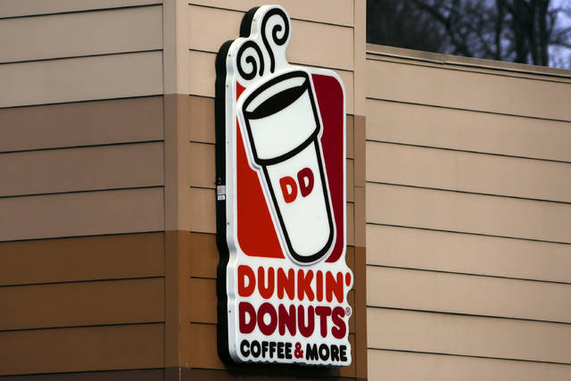FILE- This Jan. 22, 2018, file photo shows the Dunkin' Donuts logo on a shop in Mount Lebanon, Pa. Dunkin' Donuts says a story and clickable coupon being shared widely online that offers free boxes of doughnuts to celebrate its anniversary is false. (AP Photo/Gene J. Puskar, File)