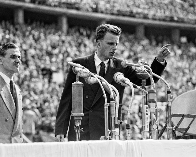 FILE - In this June 27, 1954 file photo, Evangelist Billy Graham speaks to over 100,000 Berliners at the Olympic Stadium in Berlin, Germany. Graham, who transformed American religious life through his preaching and activism, becoming a counselor to presidents and the most widely heard Christian evangelist in history, has died. Spokesman Mark DeMoss says Graham, who long suffered from cancer, pneumonia and other ailments, died at his home in North Carolina on Wednesday, Feb. 21, 2018. He was 99.
