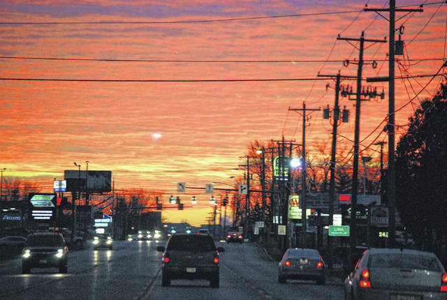 Drivers head into the City of Lima via Allentown Road in December, heading into a vivid red sky.