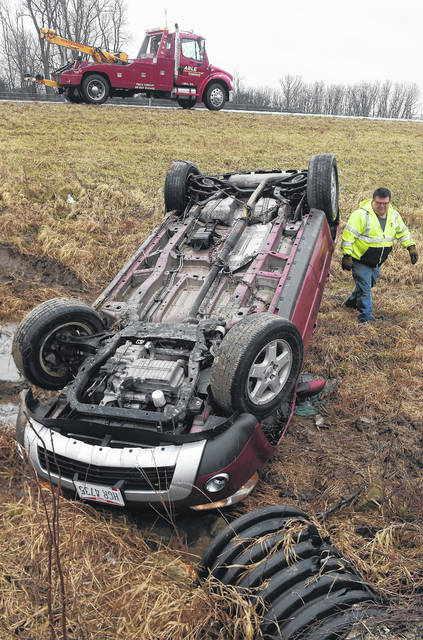 Steve Skinner, of Able Towing, prepares to remove an overturned SUV from a culvert along southbound I-75 near exit 120 in Shawnee Township on Friday. The Lima Post of the Ohio State Highway Patrol reported the SUV was southbound on I-75 at 10:02 a.m. Friday when the driver lost control. The name of the driver wasn't released Friday. The dispatcher said no one was transported to the hospital, but the driver may have been treated at the scene. Details were unavailable Friday.