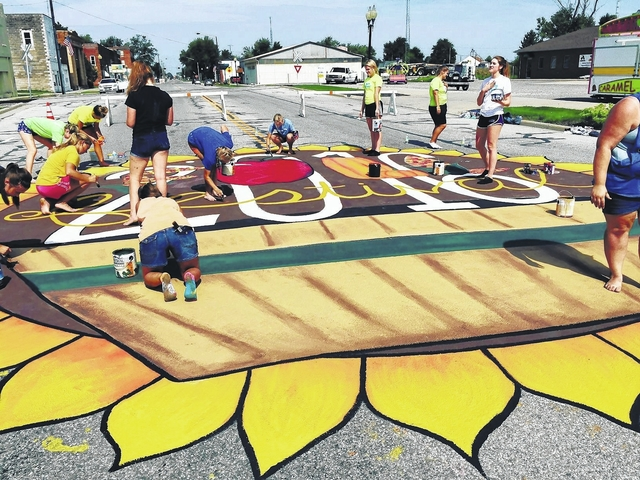 Continental High School art students paint a mural welcoming the annual fall festival in the Putnam County village.