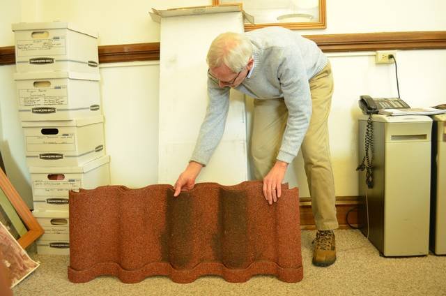 Jackson Betscher, Putnam County Administrator, examines a lightweight metallic tile, one possible option for replacing the Putnam County Courthouse roof tiles, provided by Kevin Niese, project manager and firm partner with Technicon Design Group Inc., during a Putnam County Commissioner meeting Thursday. The commissioners are examining options to fix major problems with the courthouse exterior and interior. Niese provided a rough estimate of a little over $1.08 million to complete the project during the meeting.