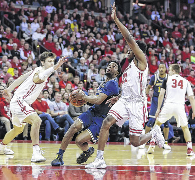 Michigan's Zavier Simpson, center, drives past Wisconsin's Ethan Happ, left, and Khalil Iverson during the first half of an NCAA college basketball game Sunday, Feb. 11, 2018, in Madison, Wis. (AP Photo/Andy Manis)