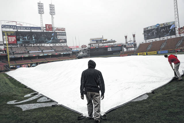 Groundskeepers place a tarp Thursday on the field at Great American Ballpark in Cincinnati where the first game of the regular season between the Reds and Washington was postponed due to rain until today.