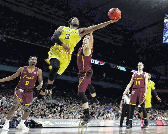 Michigan's Xavier Simpson, a Lima Senior graduate, drives to the basket between Loyola-Chicago's Donte Ingram, left, and Clayton Custer during the first Final Four semifinal Saturday in San Antonio.
