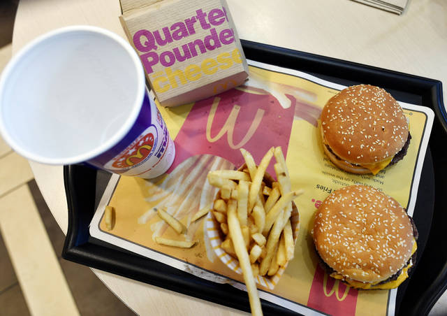 A McDonald's Quarter Pounder, top right, and Double Quarter Pound burger are shown with fresh beef Tuesday, March 6, 2018, in Atlanta. McDonald's is offering fresh beef rather than frozen patties in some burgers at thousands of restaurants, a switch it first announced about a year ago as it works to appeal to customers who want fresher foods. (AP Photo/Mike Stewart)