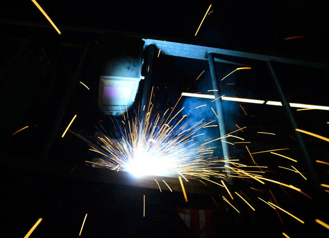 """A welder fabricates a steel structure at an iron works facility in Ottawa, Ontario, Monday, March 5, 2018. President Donald Trump insisted Monday that he's """"not backing down"""" on his plan to impose stiff tariffs on imported steel and aluminum. Trump said that Canada and Mexico would not get any relief from his plan to place the tariffs on the imports but suggested he might be willing to exempt the two longstanding allies if they agreed to better terms for the North American Free Trade Agreement. (Sean Kilpatrick/The Canadian Press via AP)"""