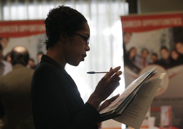 In this Tuesday, Jan. 30, 2018, photo, Joana Dudley, of Lauderhill, Fla., looks at her list of job prospects at a JobNewsUSA job fair in Miami Lakes, Fla. On Wednesday, March 7, 2018, payroll processor ADP reports how many jobs private employers added in February. (AP Photo/Lynne Sladky)