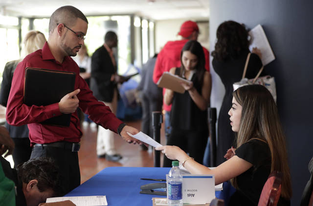 In this Tuesday, Jan. 30, 2018 photo, an employee of Aldi, right, takes an application from a job applicant at a JobNewsUSA job fair in Miami Lakes, Fla. On Wednesday, March 7, 2018, payroll processor ADP reports how many jobs private employers added in February. (AP Photo/Lynne Sladky)